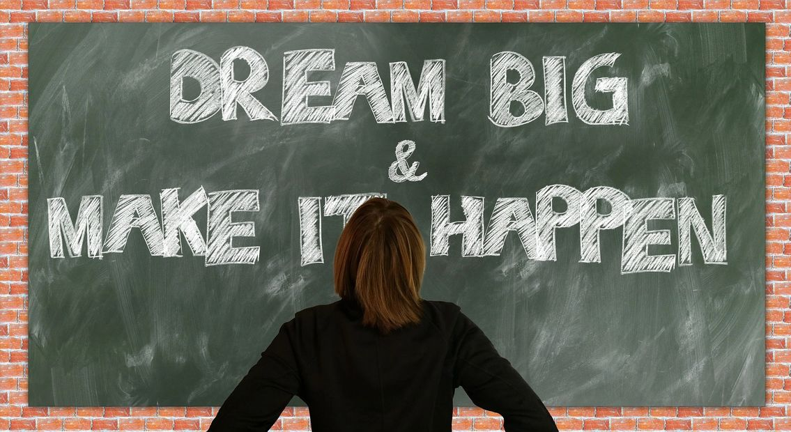 Woman standing in front of chalkboard that says Dream Big & Make it Happen