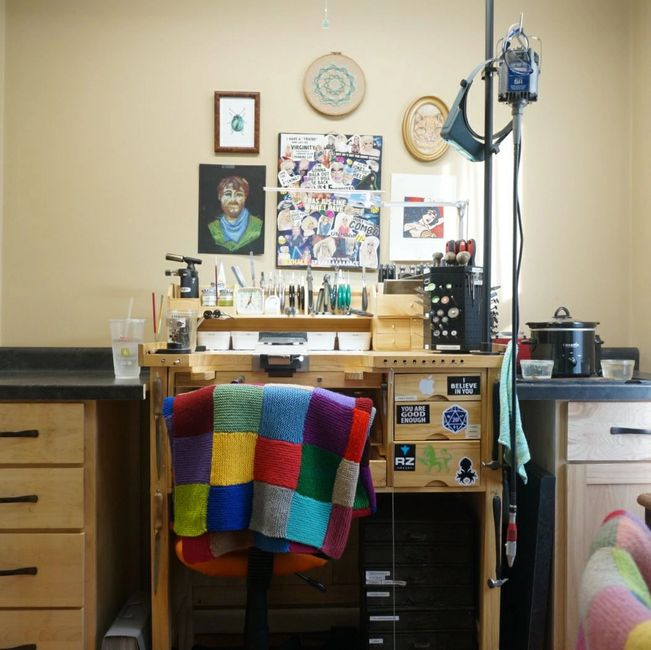 Jeweler's workbench and surrounding workspace with colorful knitted blanket on back of chair