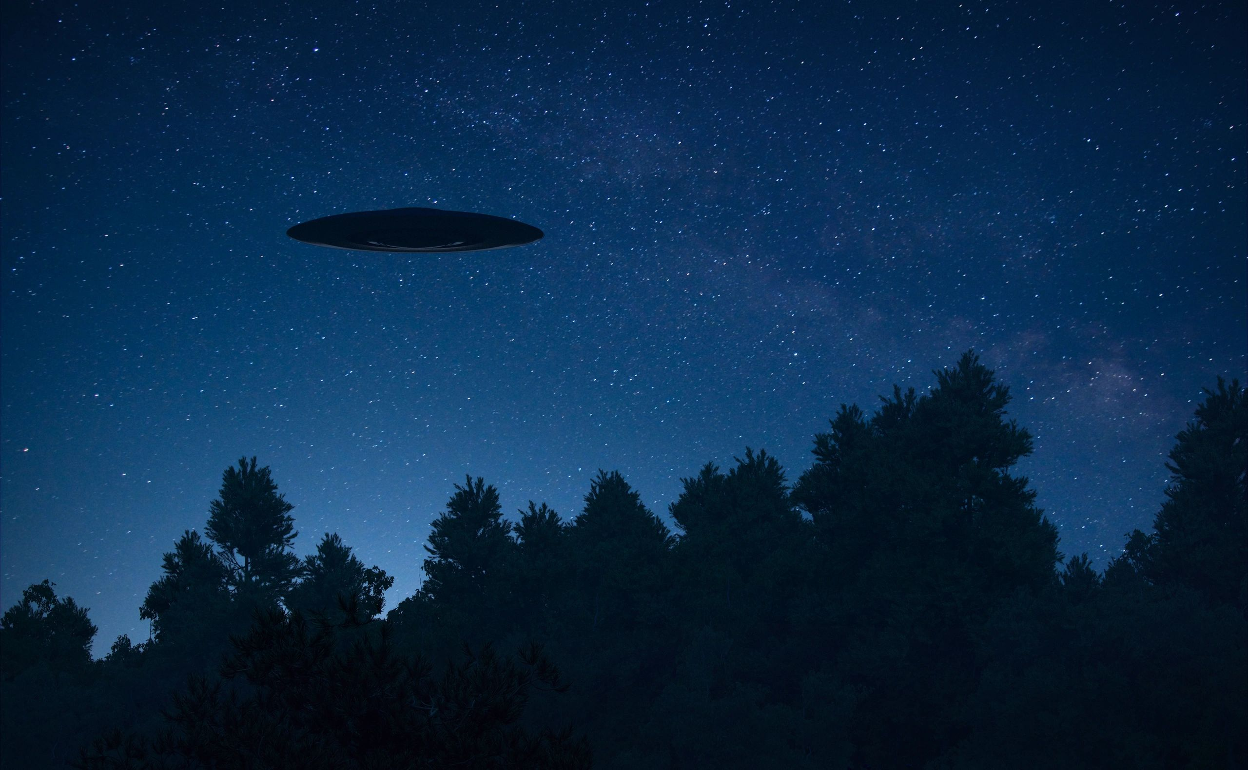Saucer silouette hovers over trees against a backdrop of stars in the night sky.