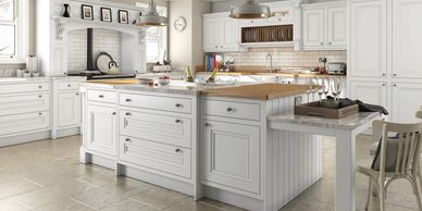 Oak kitchen design in white with hand carved corbels above range cooker.