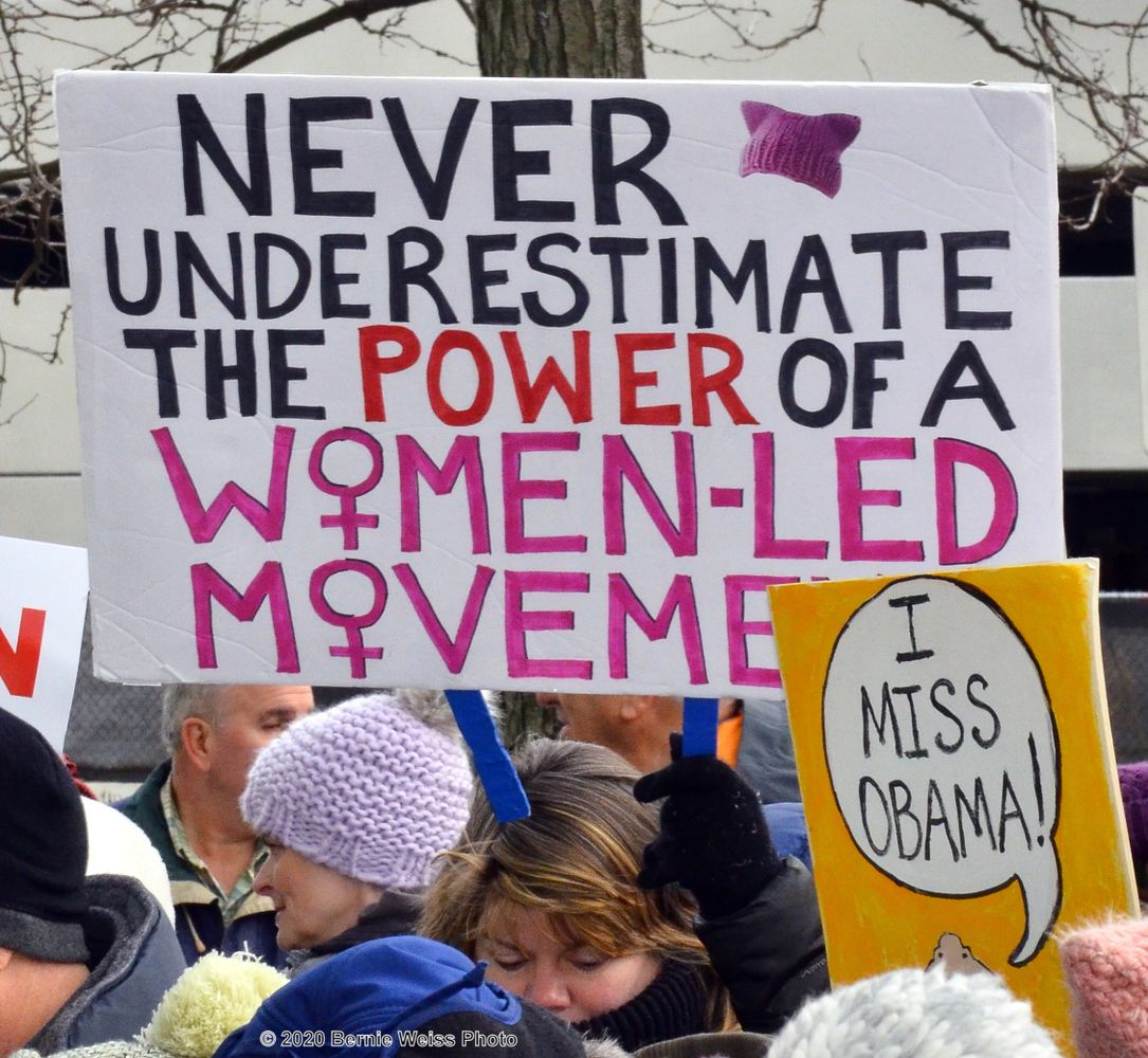 "Image of a rally, with a sign reading ""Never underestimate the power of a women-led movement."""