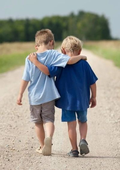 Two young boys walking down dirt road; friendships are positive.