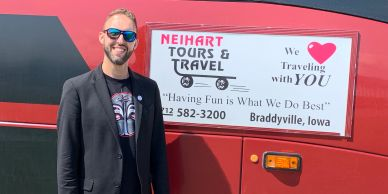 Tour guide in front of tour bus