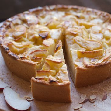 Juicy apple filling on crust-pastry base with fresh apple slices  Decorated with almond flakes.