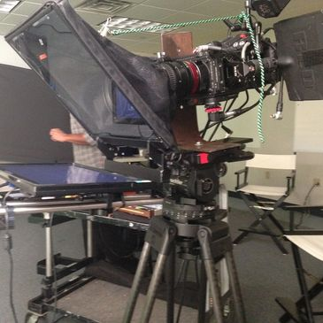 A Red camera is mounted sideways, with a rod-based TelePrompTer in front.