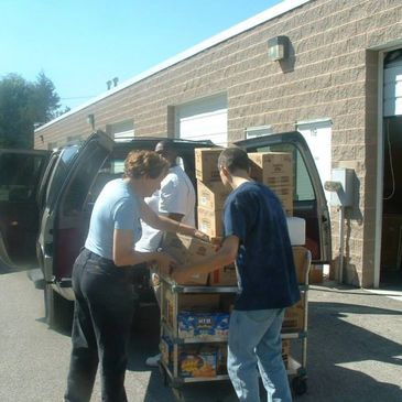 Volunteers removing boxes of donations from a car