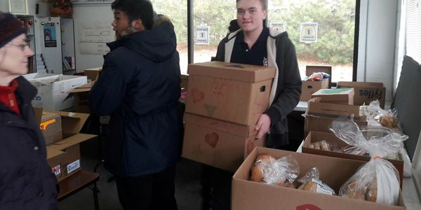 Individuals carrying boxes of food