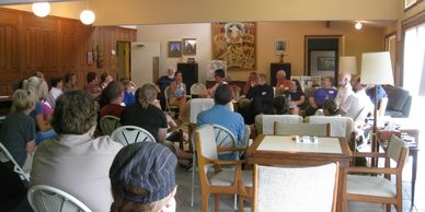 Group of retreat and seminar attendees sitting in monks rec room.
