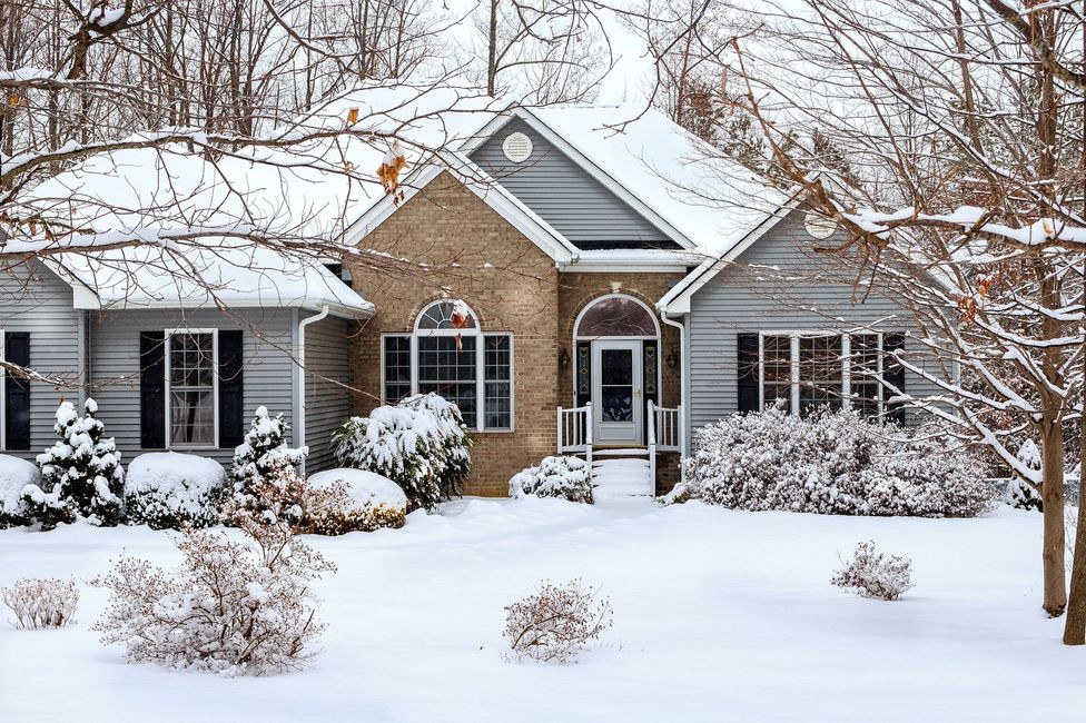A gray house with brick front and snow in winter.