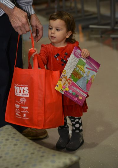 A little girl looking at her bag of toys at Toys For Our Troops