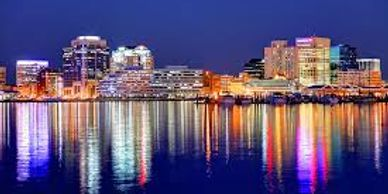 Beautiful picture of downtown Norfolk with city lights reflected off the water. Moving help