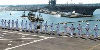 Navy Sailors dressed in white uniforms standing in military formation facing a aircraft carrier.