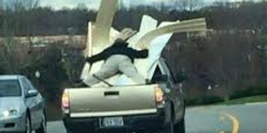 man lying atop furniture on back of truck to keep it from flying off.