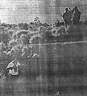 Bend Buletin photograph showing the crime scene photographer and officers standing above.