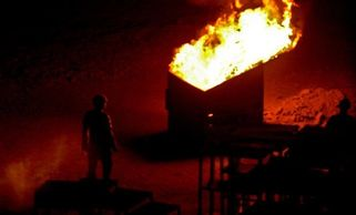 Soldiers burn trash in an old dumpster at Joint Security Station Adl in western Baghdad in 2008.