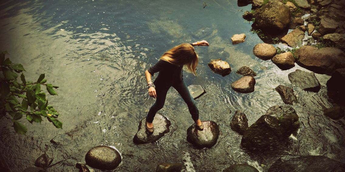Girl walking over stepping stones in water- Photo Courtesy of Daniel I Obubo, with thanks.