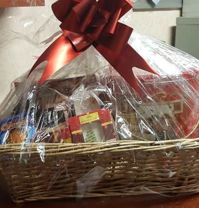 Christmas Hamper tied with ribbon, containing biscuits, christmas pudding and chocolate