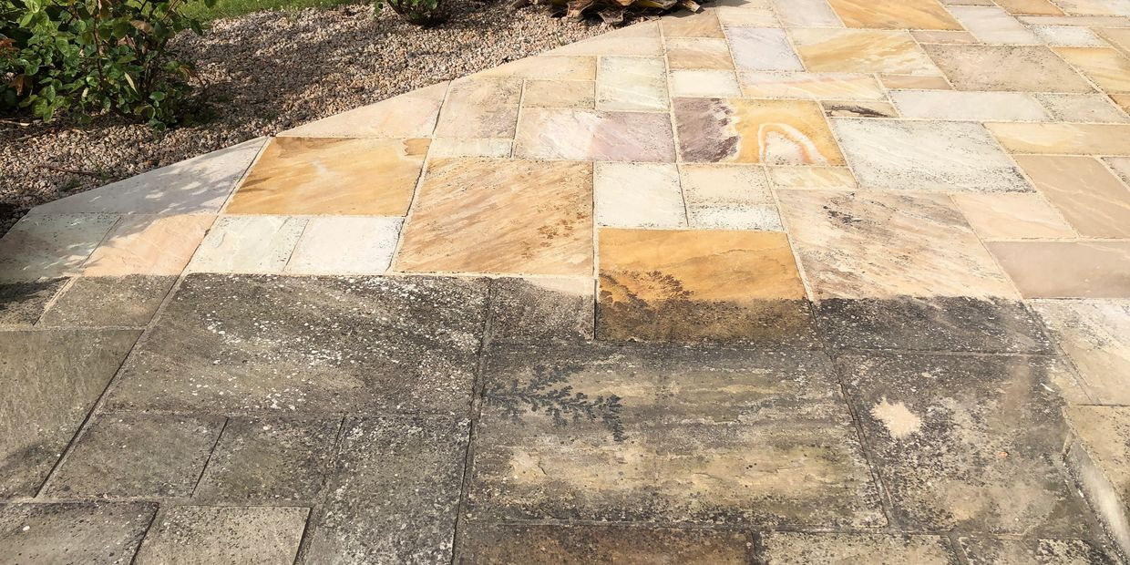 Natural stone patio partially pressure washed and treated to show how well the surface can look