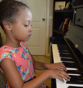 Girl taking piano lessons. Student learning the piano with teacher.