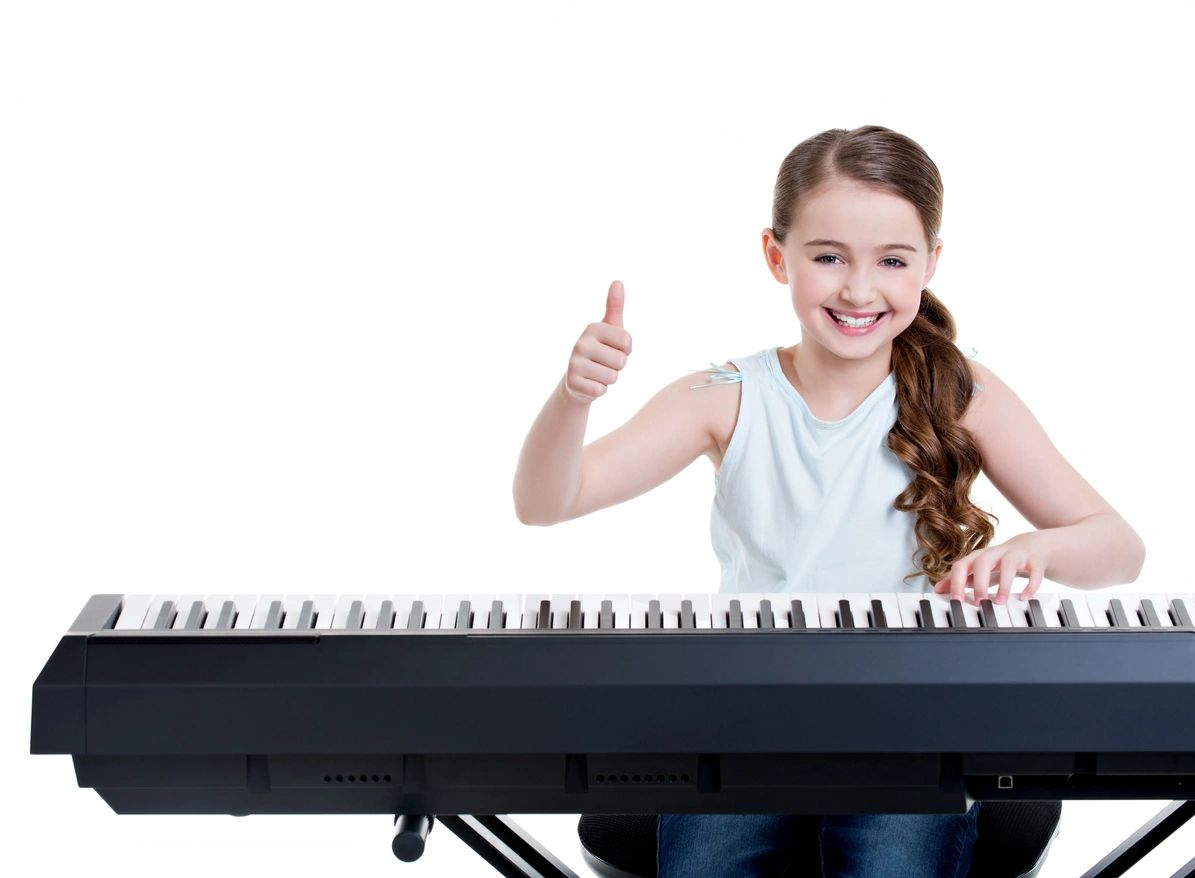 Girl is happy while sitting at the piano.