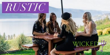 Women sitting around picnic table overlooking lake, drinking wine