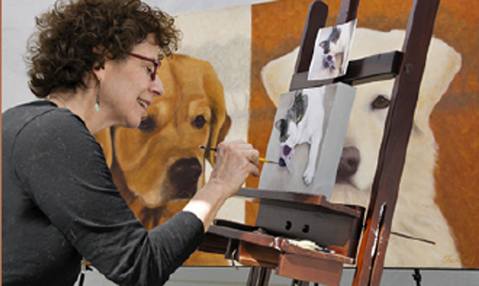 Shelley Lowell painting a portrait  of a cat with her painting of dogs  in the background.