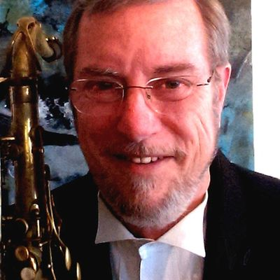 Dave Jones with sax and one of his paintings in the background.