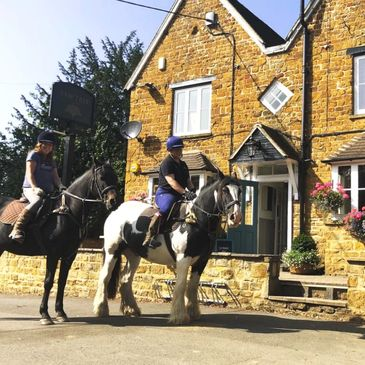 Two ladies on horseback outside of the Yew Tree pub