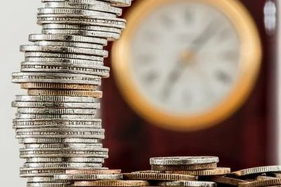 Stack of coins with a clock in the background