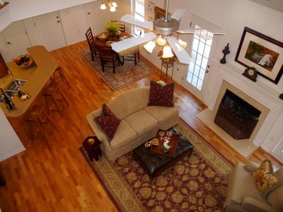 View of beautiful hardwood floors and fireplace from balcony bridge above