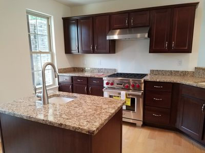 Chefs kitchen with granite countertops and high-end appliances