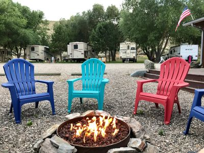 Community fire pit and rv sites on grass.