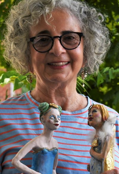 Judith Maier, local artist and sculptor, holding two of her ceramic companions
