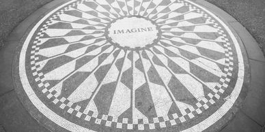 "Black and white Mosaic circle with the word, ""Imagine"" in the center"