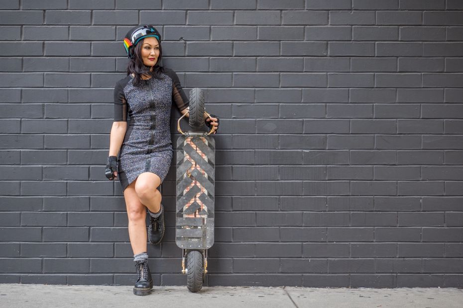Mary Christina Brown standing next to a two wheel electrical skateboard called SpeedBoard. #esk8
