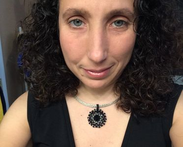 Woman wearing black mandala pendant