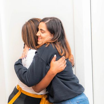Friends hugging at an empowerment event