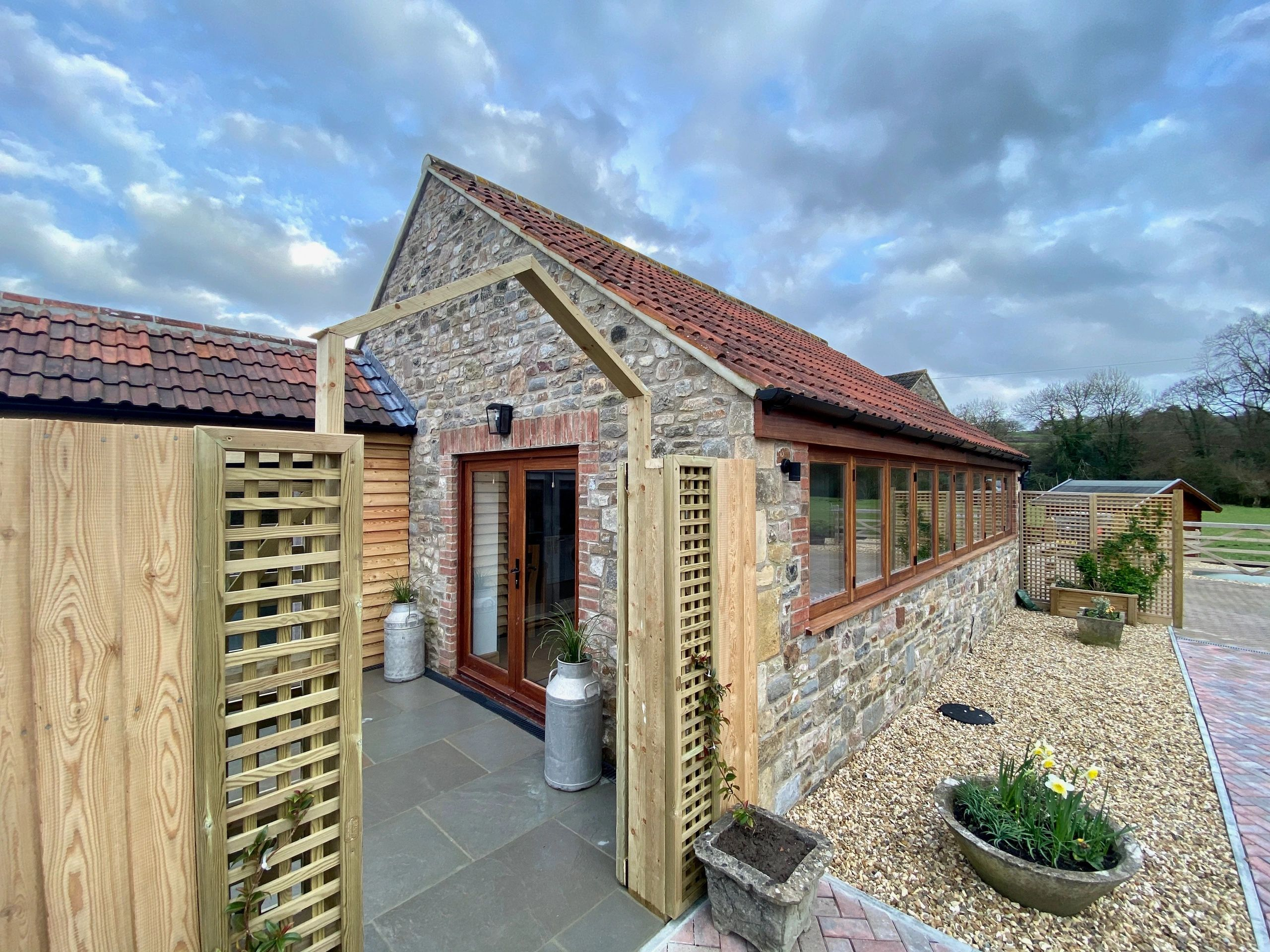 A one bedroom cottage with a courtyard area with patio furniture and a shed for storage.