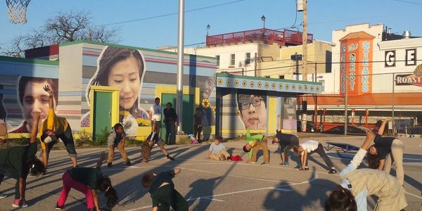 Image of Capitolo Playground mural with kids steching in the foregound.