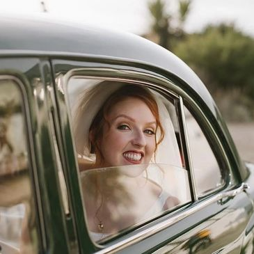 Beautiful Bride smiling in wedding car