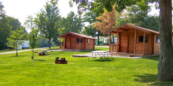 Two log cabins with picnic tables and fire rings in front.