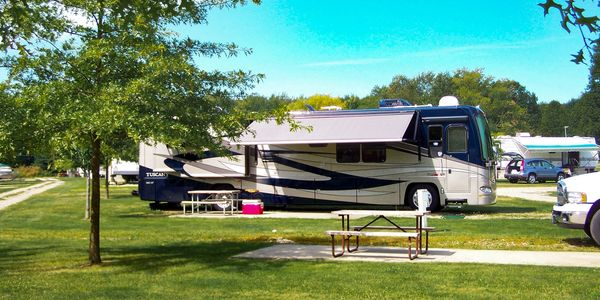 Motorhome parked in camping spot with awning extended.