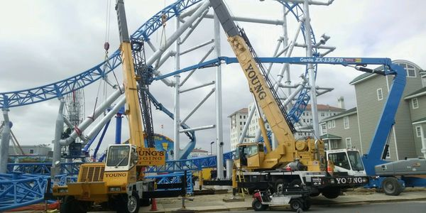 Using crane lifts to erect a roller coaster at an amusement park.