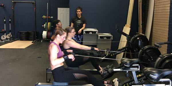 CrossFit class rowing on Concept 2 Ergs.