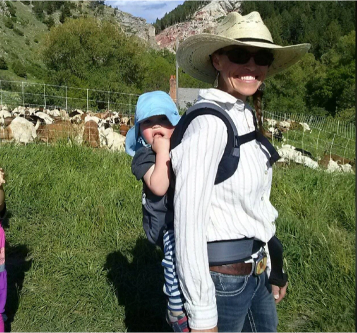 A young woman with child in a backpack and goats in the background.