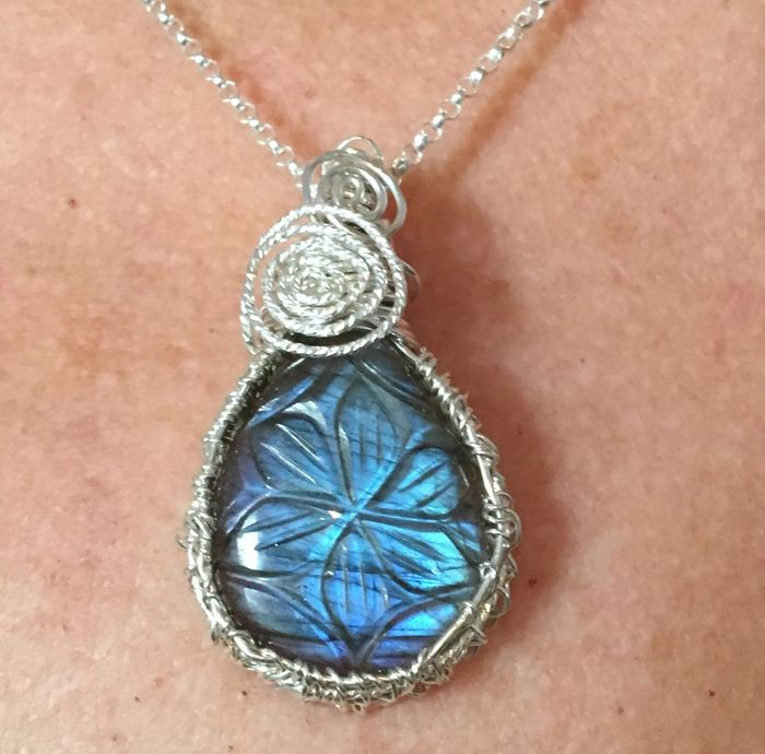 Hand carved Labradorite cabochon, hand wrapped in sterling silver wire featuring swirls.