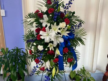 Blue Delphinium, White Lilies, Red Roses, and carnations present a stunning patriotic tribute.
