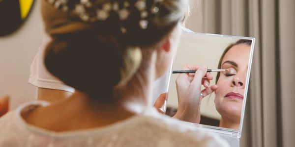 Bride getting her finishing touches done to her bridal makeup and bridal hairstyle