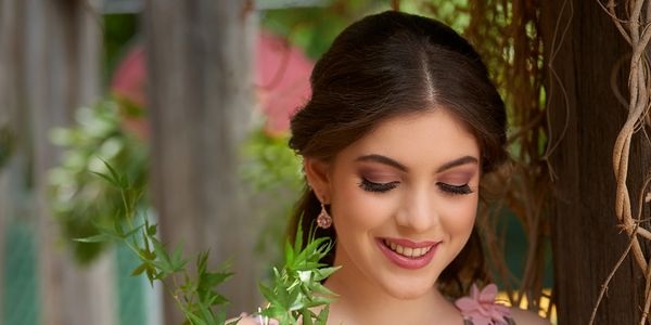 Bridesmaid smiling in a floral dress, wearing beautiful bridal makeup bridal bouquet and bridesmaid dress