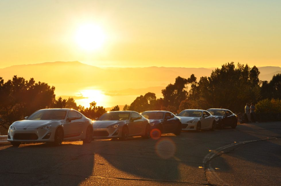 Row of sports cars parked at sunset